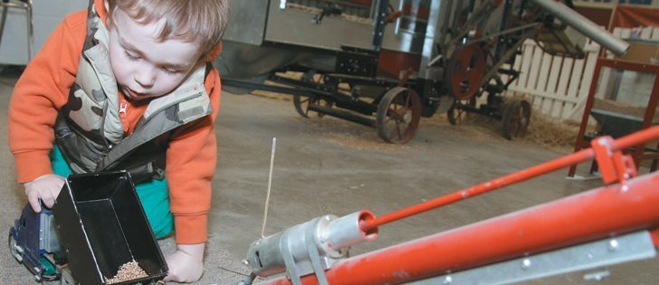 Zachary Young, 3, of La Riviere, Man., dumps wheat from a model truck into a miniature grain auger at the Royal Manitoba Winter Fair.  |  Robert Arnason photo