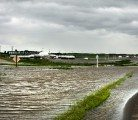 Flood water flows over a grid road on the south side of Highway 16, 3 Km. west of Foam Lake, Sask.  |  Robin Booker photo