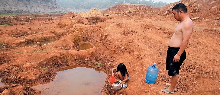 A girl collects water from a puddle at a dried-up reservoir as her father stands beside her in China's Henan province July 30. Lingering droughts in most parts of China have affected millions of acres of agricultural crops.  |  REUTERS photo