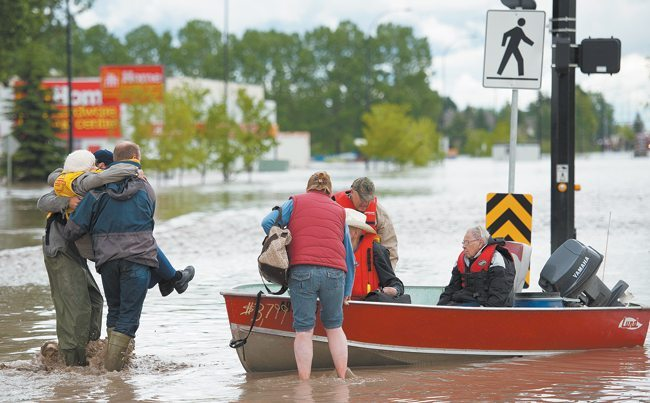 A woman is rescued by boat in High River, Alta. A state of emergency was declared in the town and residents were evacuated.  |  Mike Sturk photo