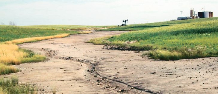 A 50-year-old saltwater spill in North Dakota leaves the soil bare of plants. Brine spills can occur on or off oil well pads, causing damage to equipment and taking portions of land out of agricultural production. Prairie cropland is considered to be severely saline if the electrical conductivity is 15.  Sea water has an EC of 40 to 50. The brine from fracking has an EC well over 200.  |  Aaron Daigh/NDSU photo