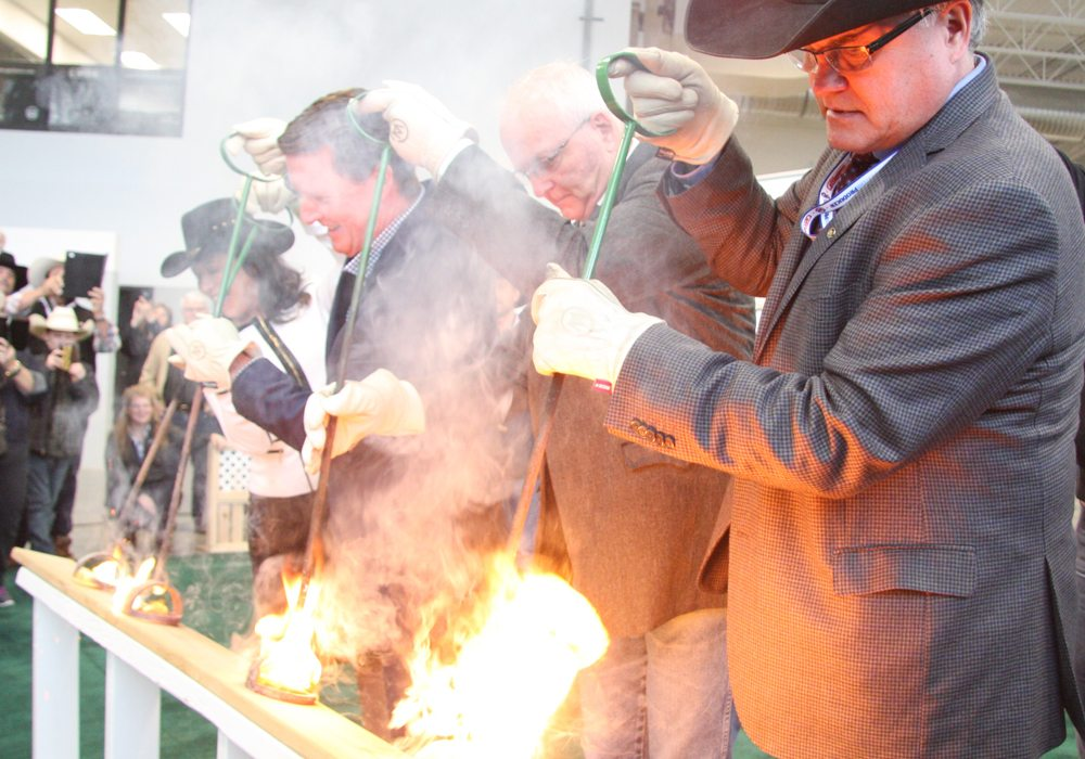 From left, Tracy Fahlman, CEO of Regina Hotels Association, Regina mayor Michael Fougere, Saskatchewan agriculture minister Lyle Stewart and Canadian Western Agribition president Bruce Holmquist burn the brand to open the 2017 show and celebrate the opening of the International Business Centre. | Karen Briere photo