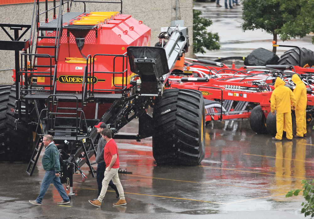 A couple of farmers came prepared last week as rain fell on Canada's Farm Progress Show in Regina. The show disappointed some visitors and exhibitors, but organizers say they have a plan.  |  Michael Raine photo
