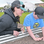 Friends of the Greenhouse volunteer Janet Boyd, who graduated from the high school in 1999, and her son, Ruben Boyd-Hunter, plant parsnip and turnip seeds in one of the raised beds at the EcoVision garden. The raised beds are made from two corrugated window wells bolted together. A half bale of alfalfa hay is then laid in the frame to retain moisture and provide nutrients and covered with planting soil. Boyd also shows teachers how to start tower gardens in the classroom.  |  Maria Johnson photo