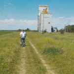 Mark Kihn stands in front of an old grain elevator at Clanwilliam, Man., which is no longer standing.  |  Brian Nicholls photo