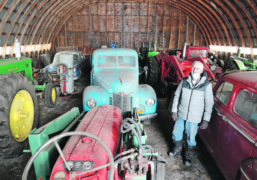 Marv Vassberg of Bawlf, Alta., stands in his shed with some of the dozens of tractors, cars and trucks he has rebuilt.  |  Mary MacArthur photo